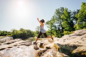Caucasian woman jumping on rocks near river